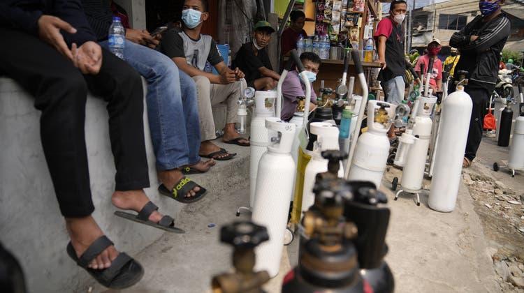 Die Schweiz unterstützt Indonesiens Kampf gegen Corona mit einer Hilfsgüterlieferung. Im Bild warten Bürger in Jakarta auf Sauerstoff. (AP)