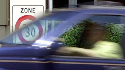 Ein Autofahrer passiert in Zürich ein Zone 30-Verkehrsschild. (Steffen Schmidt / KEYSTONE)