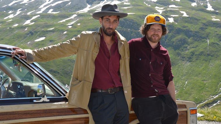 Mario Schelbert alias «Moe»der Band Moes Anthill (rechts) mit Schauspieler Peter Zgraggen. Sie lehnen an einen altenTown & Country von Chrysler. (Bild: Kristina Gysi (Furkapass, 23. Juli 2021))