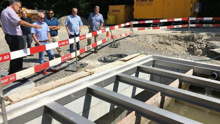 Das neue Regenklärbecken bei der ARA in Bremgarten: Abwasserverbandspräsident Pius With(links) präsentiert das Bauwerk vor der Eröffnung den Gemeindevertretern. (Walter Christen)