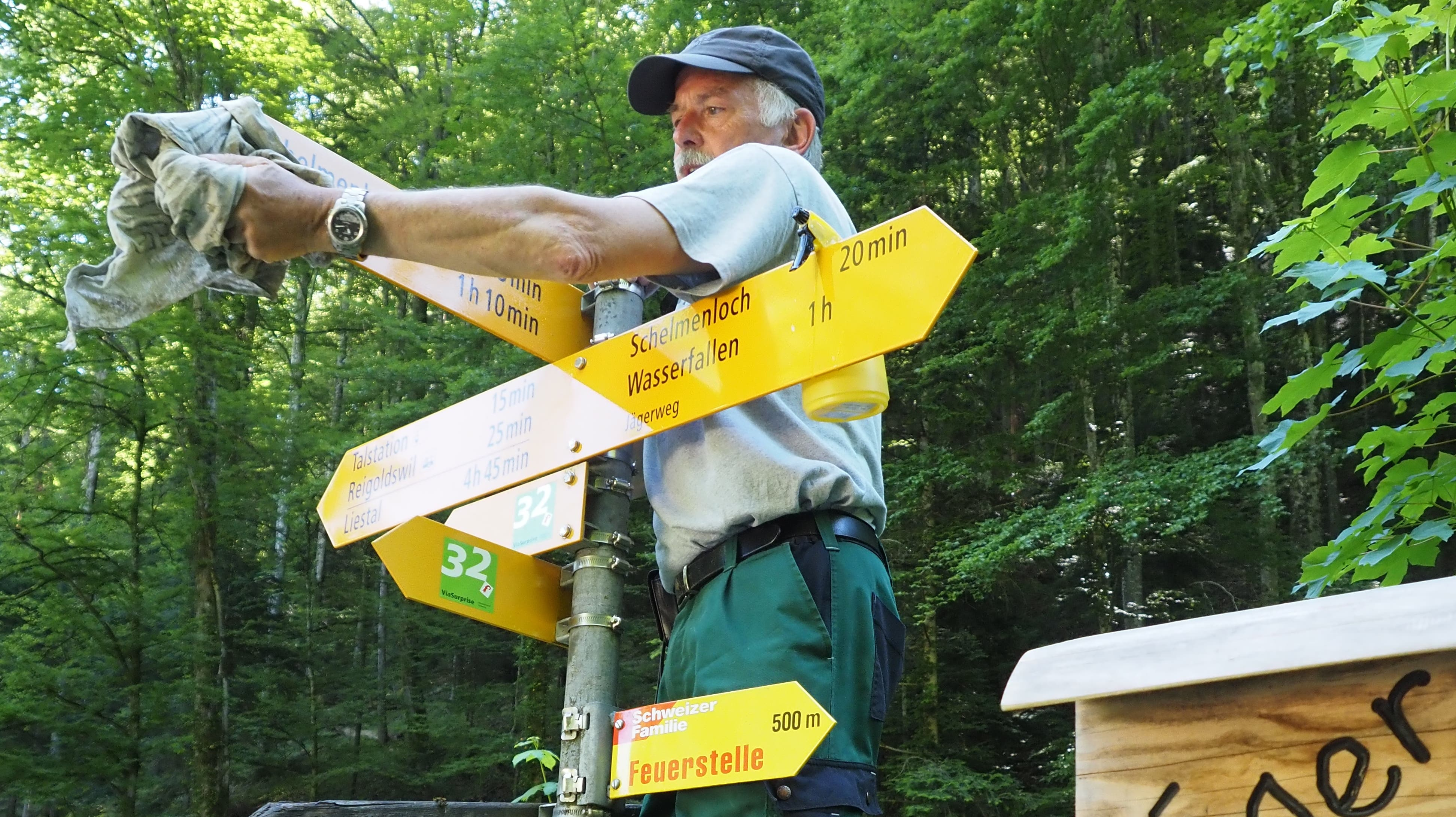 Der Ziefner Hansueli Schaub putzt den Wegweiser am Beginn des Jägerwegli in Reigoldswil mit Essigwasser und Putzlappen.