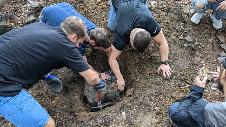 Ehemalige Mitglieder der Jungwacht Balsthal graben einen alten Gruppenschatz im Balsthaler Wald aus. (zvg)