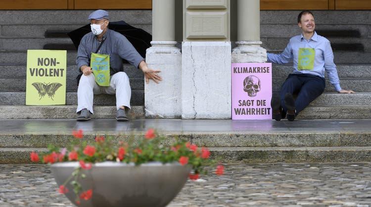 Zwei Aktivisten haben ihre Hände an die Säulen des Bundeshauses geklebt. (Keystone)