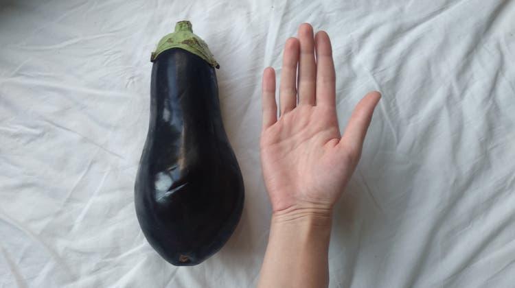 Aubergine heisst immer Aubergine, egal ob man sie streichelt oder isst. Hier sehen sie ein Bild der grössten Aubergine der Alpennordseite, Hand der Autorin als Grössenvergleich. (Bild:Samantha Zaugg)