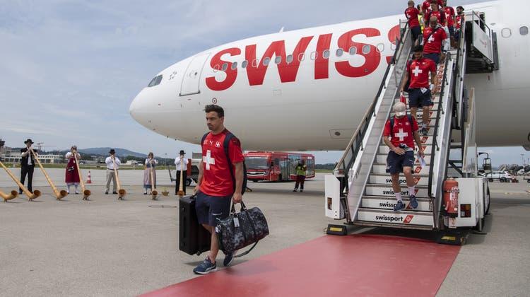 Die Spieler (vorn: Xherdan Shaqiri) verlassen, von Alphörnern begleitet, das Flugzeug. (Keystone)
