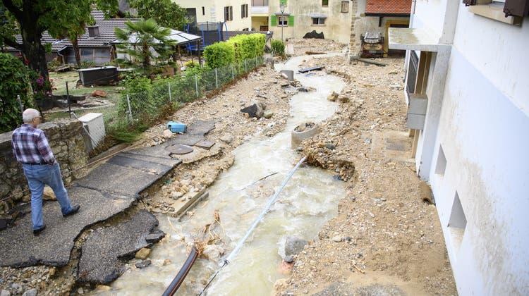 Schlamm- und Wassermassen verwüsteten Strassen und Häuser in Cressier. (Keystone)