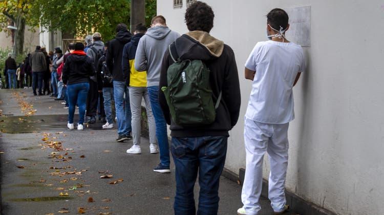 Menschen stehen Schlange vor dem Corona-Testzentrum des Universitätsspitals Basel. (Archivbild: Keystone)