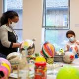 Zwei Teilnehmerinnen der Kreativwerkstatt im Kunstmuseum kleistern farbige Ballone. (Bild: Tobias Garcia)