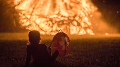Ein Kind mit Lampion blickt aufs Funkenfeuer. (Bild: PD)