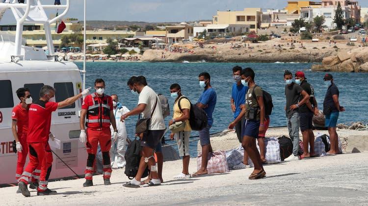 Migranten besteigen ein Schiff der italienischen Küstenwache. (Archivbild September 2020) (AP/Mauro Seminara)