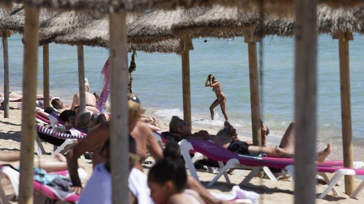 Touristen sonnen sich auf Mallorca: Die Insel will trotz steigender Coronazahlen keine neuen Einschränkungen verhängen. (Francisco Ubilla / AP)