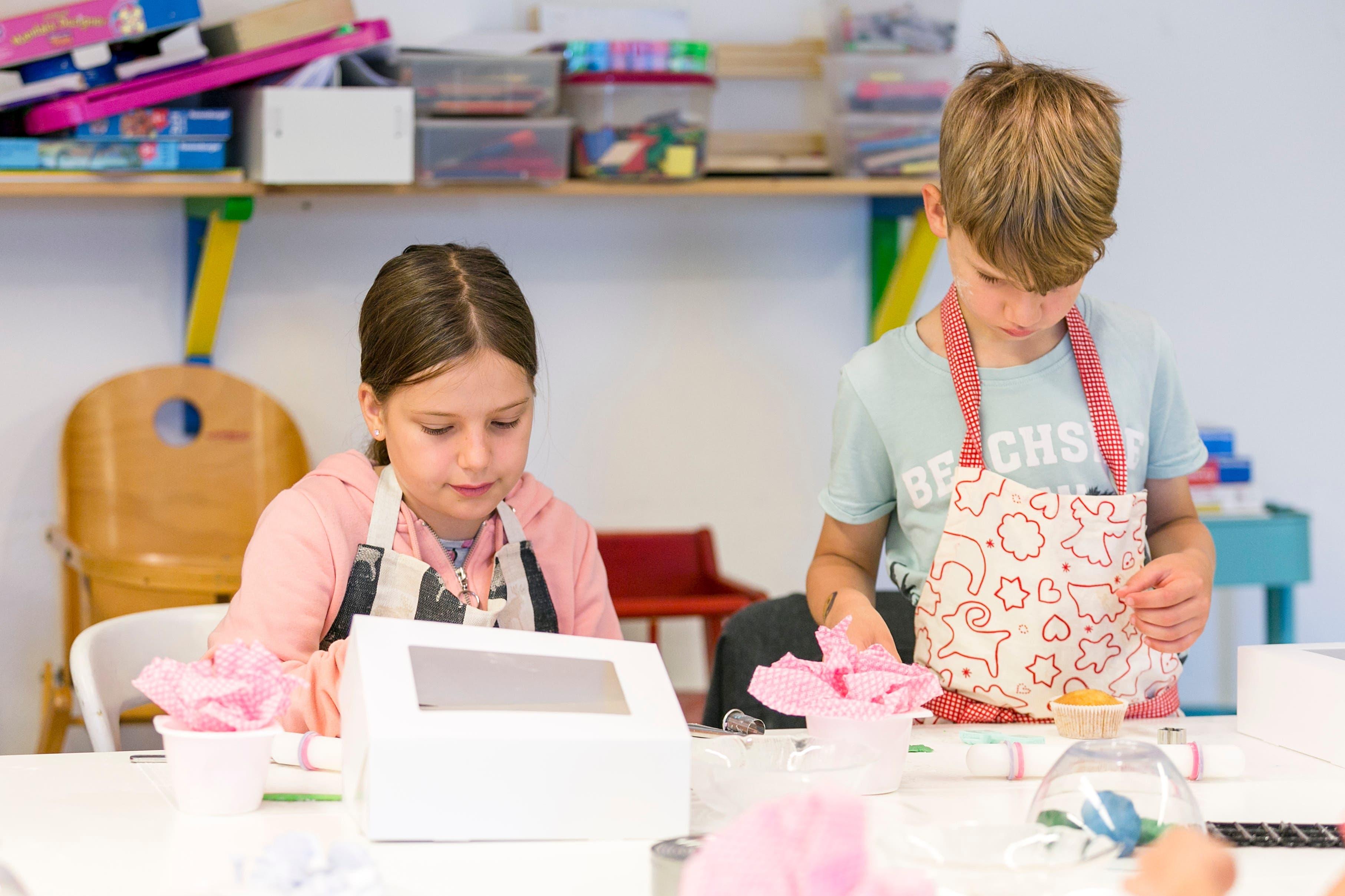 Die zehnjährige Mina und der achtjährige Robin sind konzentriert am Verzieren. Die Werkzeuge konnte Kursleiterin Elena Ciglic von ihrer Kollegin ausleihen.