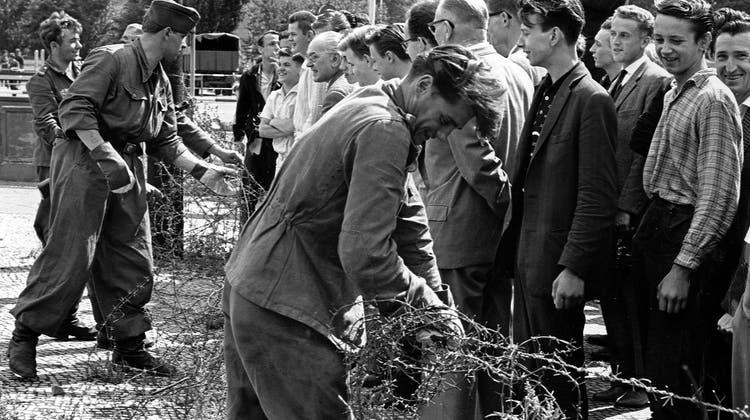 13. August 1961: DDR-Grenzer ziehen an der Sektoren-Grenze Stacheldrahtzäune hoch. Dass die Trennung 28 Jahre dauern wird, konnte niemand ahnen. (Keystone)