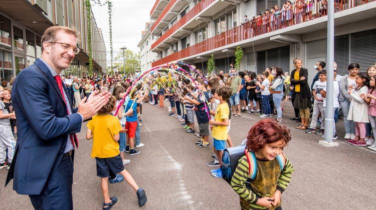 Geschafft: Ein Schüler der Klasse 1a läuftunter Applaus des Lysbüchel-Schulhauses und Erziehungsdirektor Conradin Cramer (l.) zu seiner neuen Lehrerin. (Nicole Nars-Zimmer)