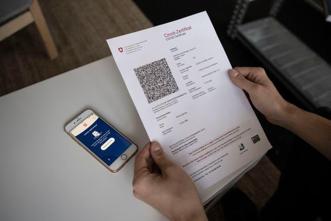 Das Covid-Zertifikat Schweiz wird mit einem Mobiltelefon eingescannt.