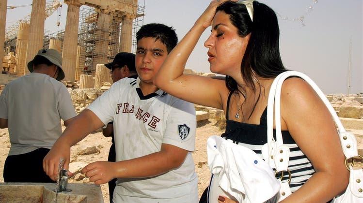 Eine Touristin verfolgt eine traditionelle Wachablösung in der Athener Altstadt. In Griechenland klettern die Temperaturen heute auf bis zu 47 Grad. (Keystone)