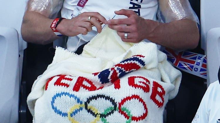 Turmspringer Tom Daley strickt sich die Accessoires zu seiner Goldmedaille in Tokyo gleich selbst - während er seine Muskeln kühlt. Die Aufmerksamkeit hat er so auf sicher, auch wenn vor ihm schon mancher Cowboy seine Decke selbst strickte. (Clive Rose / Getty Images AsiaPac)