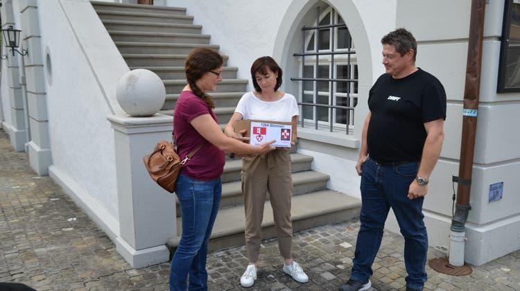 Vereinspräsidentin Rahel von Wyl (links) und Vizepräsident RenatoBurch übergeben die Unterschriften vor dem Sarner Rathaus an Landschreiberin Nicole Frunz. (Bild: Martin Uebelhart (Sarnen, 2. August 2021))