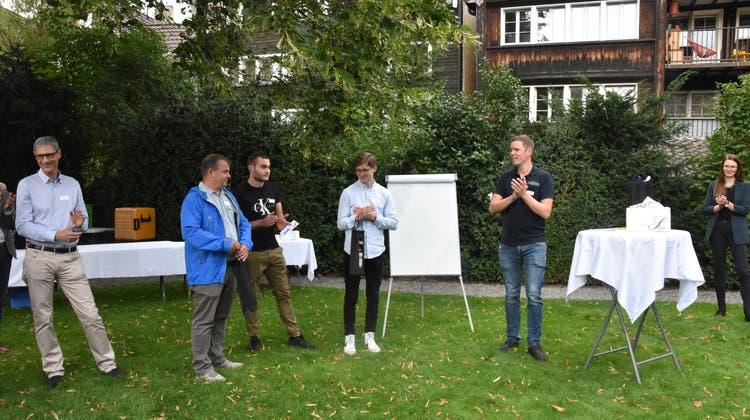 Ralph Nessensohn (rechts) ehrt die beiden Lernenden Steven Coray und Luca Zürcher und überreichte auch dem Lehrmeister ein Geschenk. (Bild: rak)