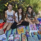 Alessia, Belina und Kyla verkaufen Barbiepuppen und Feenkleider. (Bild: Maya Heizmann)