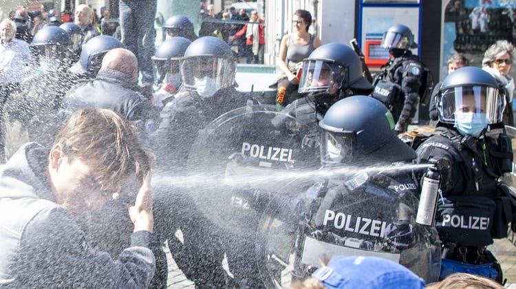 Demoverbot in Bern: Die Polizei kesselt eine Kundgebung gegen die Coronamassnahmen ein und löst sie später auf. Ein Polizist trägt eine Tulpe im Gurt, die ihm eine Demonstrantin geschenkt hat. (Bild: Raphael Hünerfauth, Bern (20.März 2021))