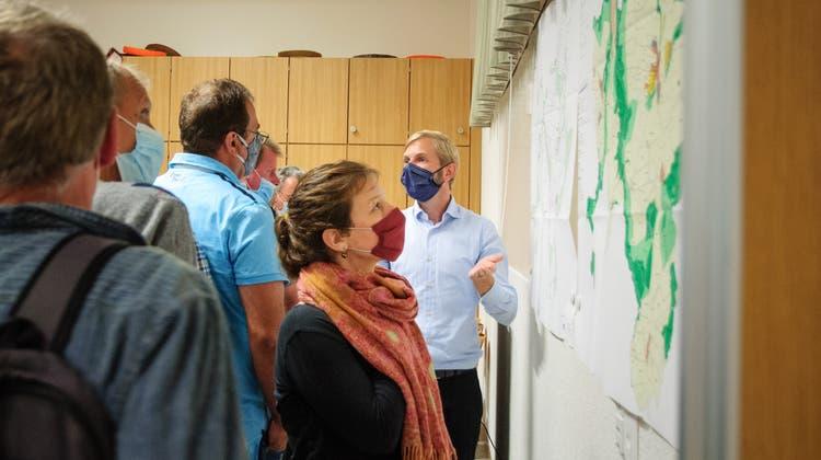 Thomas Tschopp (blaues Hemd) von der NRP Ingenieure AG erklärt den Interessierten die neuen Pläne aus der Ortsplanungsrevision. (Bild: Sabrina Bächi)
