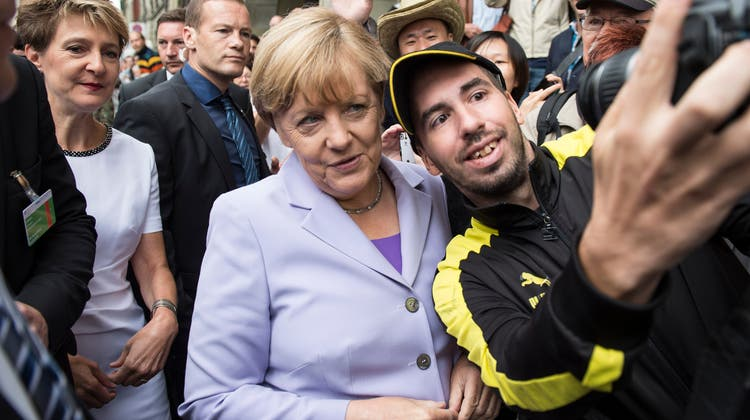 Ein Unbekannter macht 2015 in Bern ein Selfie mit Bundeskanzlerin Angela Merkel (vorne) und Bundespräsidentin Simonetta Sommaruga. (Keystone (Bern, 3. September 2015))