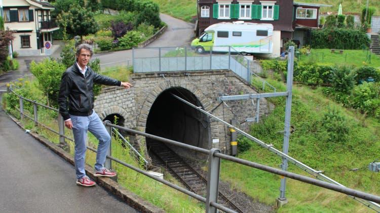 Armin Zöggeler zeigt aufs Südportal des Wasserfluhtunnels. (Bild: Martin Knoepfel)