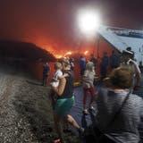 Bewohnerinnen und Touristen verlassen Euböa auf einer Fähre, während die Feuersbrunst sich dem Dorf Limni nähert. (Thodoris Nikolaou / AP (6. August 2021))