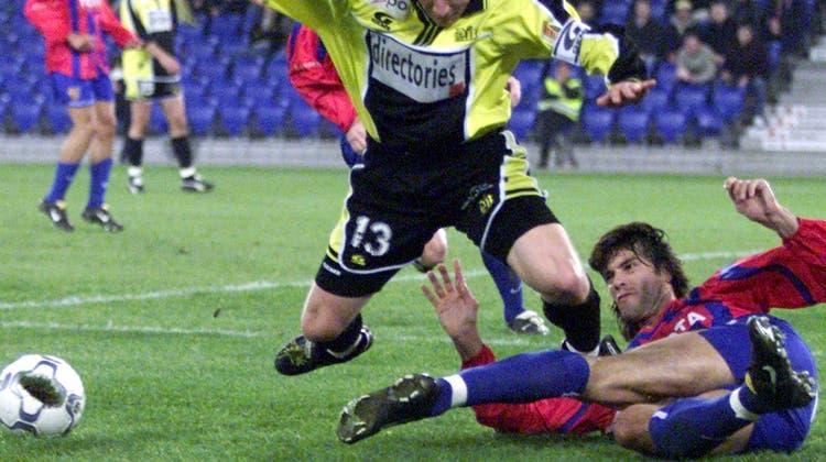 Symbolbild für ein Tackling. Der Basler Spieler George Koumantarakis am Samstag, 9. März 2002, im Basler St. Jakobpark gegen den Berner  Erich Haenzi. (Bild: Georgios Kefalas (Reuters))