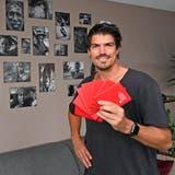 Raphael Fischer in seinem Wohnzimmer in Starrkirch-Wil: im Hintergrund Bilder von Menschen, die er auf seinen Reisen getroffen hat. (Bruno Kissling)