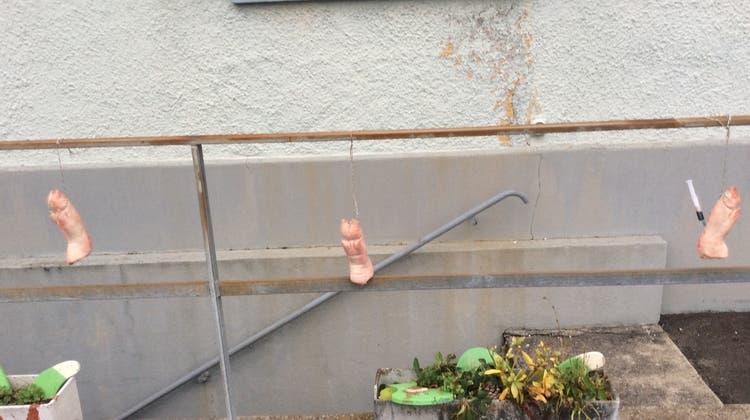 Drei Schweinsfüsse hängen am Geländer: Auf zweien ist mit Filzstift der Name «Bartel» geschrieben, auf einem steht «Ruedi». In einem der drei Schweinsfüsse steckt zudem eine Spritze. (Bild: PD)