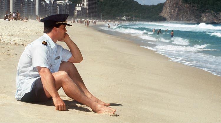 Die Schweizer Fluggesellschaft Swissair wird am 2. Oktober 2001 wegen fehlender Liquidität zum sofortigen Einstellen des Flugbetriebes gezwungen.Auf dieser Aufnahme ist Daniel Riediker, ein nachdenklicher Swissair-Pilot, zu sehen, welcher sich die Wartezeit am Strand von Rio de Janeiro versüsst. (Bild: Markus A. Jegerlehner)