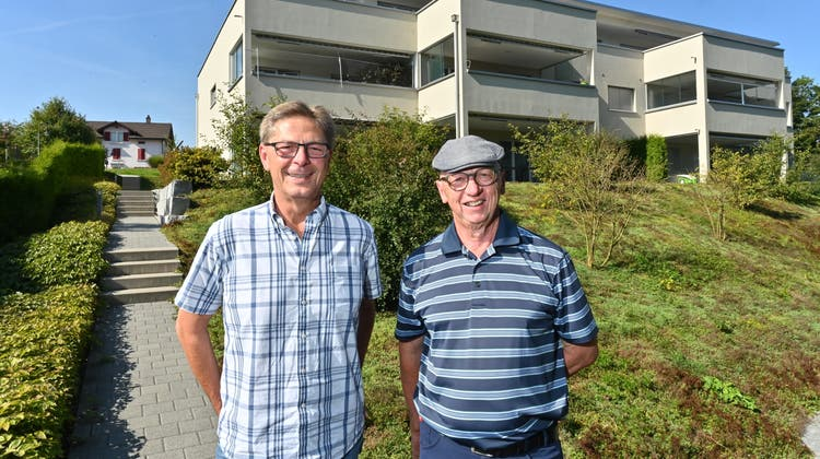 Stabübergabe von Heinz Bader (rechts) an Rainer Nussbaumer. Auf dem Bild der neuste Bau der Wohnbaugenossenschaft an der Stampfistrasse. (Bruno Kissling)