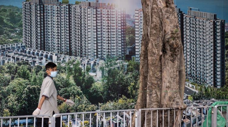 Die Aktien des chinesischen Immobilienriesen Evergrande haben massiv an Wert verloren. Im Bild: Ein Mann vor einer Werbung für das Wohnprojekt Emerald Bay in Hong Kong von Evergrande. (Jerome Favre / EPA)