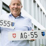Richard Spathelf vom Strassenverkehrsamt zeigt die beiden Nummern, die am Mittwochabend versteigert wurden. AG 55 schenkte richtig ein. (Bild: Alex Spichale)