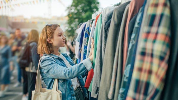 Eine junge Frau ist auf der Suche nach einem passenden Secondhand Kleidungsstück. (Bild: PD)