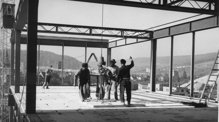 Bauarbeiter setzen eine Bodenplatte um die andere in das Stahlgerüst des Hauptgebäudes der Kanti Baden. (Baudepartement Aargau))