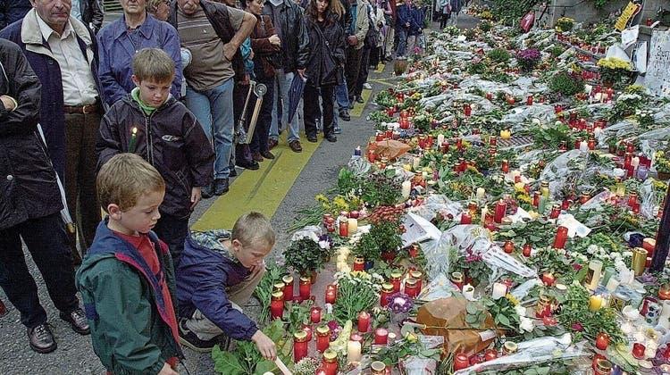 Trauernde Menschen vor dem Zuger Regierungsgebäude, in dem am 27. September 2001 bei einem Attentat 14 Menschen getötet und 18 weitere verletzt wurden. (Bild: Christof Borner- Keller (Zug, 29. September 2001))