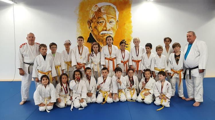 Der erfolgreiche Nachwuchs des Grenchner Judoclubs posiert vor dem des Begründers der Judo-Disziplin,Professor Jigoro Kano, im neuen Grenchner Vereinslokal. (zvg)
