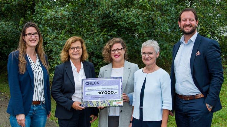Christina Hegi Kunz, Geschäftsleiterin der Dargebotenen Hand (2. von rechts), und Karim Twerenbold, Präsident des Coop-Regionalrats Nordwestschweiz (rechts), bei der Checkübergabe. (zvg/Markus Hässig)