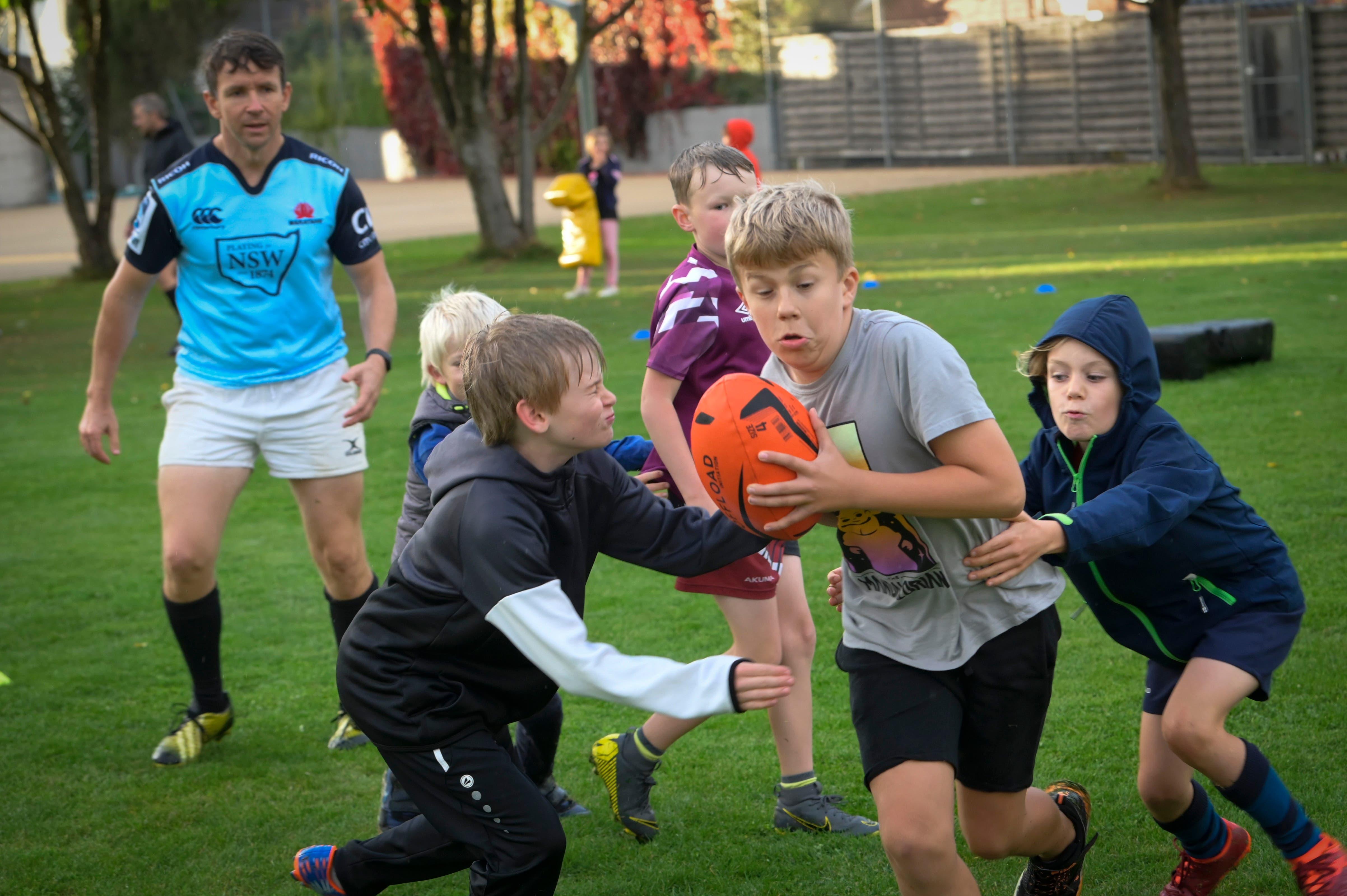 «Tackle him!», ruft Gründungsmitglied und Trainer Caleb Cooke des Rugby Club Tägerwilen, während er die Kleinen anfeuert, als sie aufeinander zurennen. Der Knabe mit dem orangen Rugbyball versucht seinen Gegnern zu entkommen, die ihn durch ein Tackle umwerfen wollen.