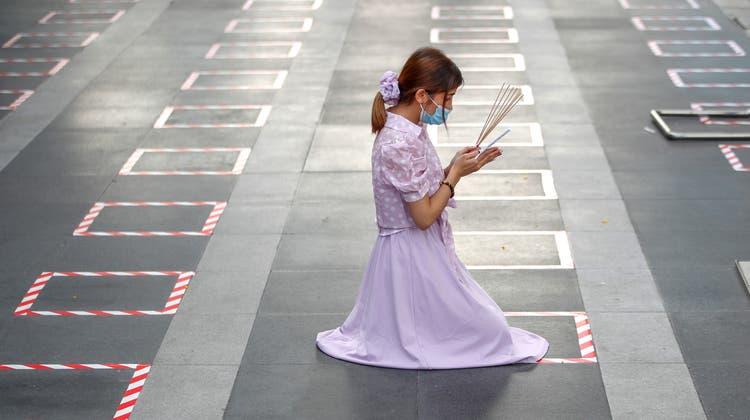 Eine Frau kniet in einem markierten Social-Distancing-Feld ausserhalb eines Shopping Centers in Bangkok, um zu beten - Thailand kämpft mit stark steigenden Corona-Infektionszahlen. (key/epa)