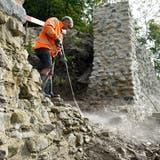 Mit der Hochdrucklanze spritzt Maurer Hazir Nrecaj ein paar Steine und Mörtel aus der Wand, um einen Durchgang für Besucher zu schaffen. (Bild: Mario Testa)