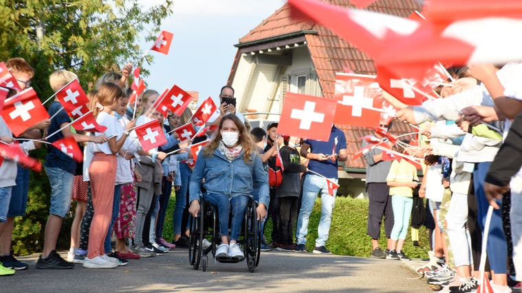 Mit lautem Jubel und wehenden Fahnen begrüssten die Schule Waltenschwil ihre Lehrerin Catherine Debrunner zurück. (Bild: Melanie Burgener)